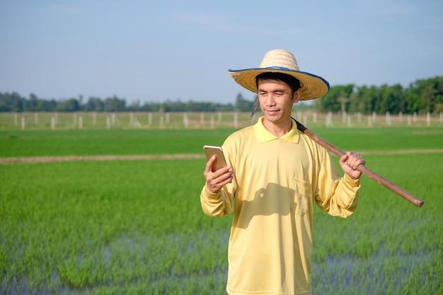 Agricultores asiáticos usam camisas amarelas usando o smartphone na fazenda verde.