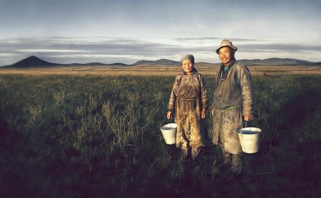 Agricultores da mongólia segurando a bacia no campo