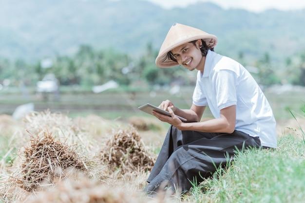 Agricultores do sexo masculino usam almofadas sentados nos campos de arroz durante o dia
