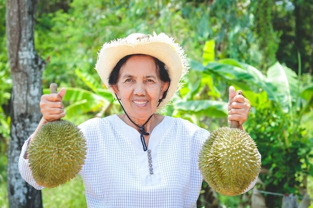 Agricultores idosos do sexo feminino asiáticos usando chapéus, segurando 2 frutas durian