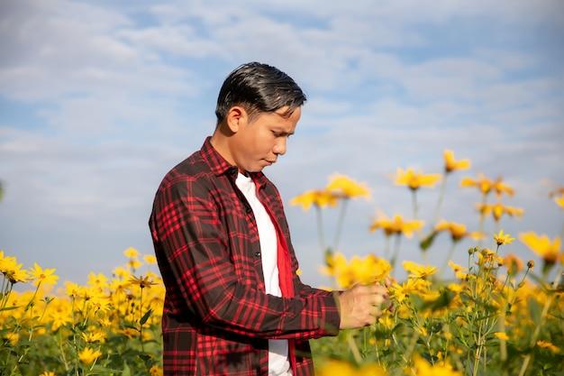 Agricultores inspecionam a fazenda de flores de verão ensolarado.