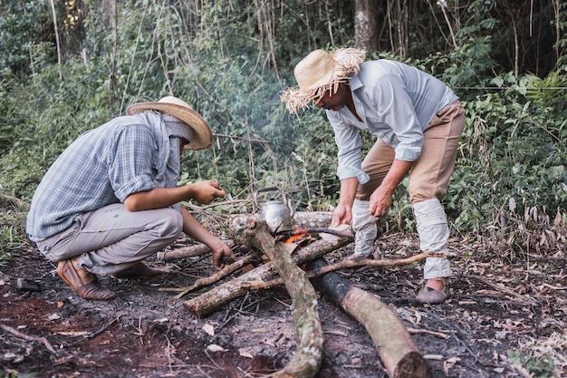 Agricultores locais fazendo fogo para aquecer água em uma chaleira rústica.
