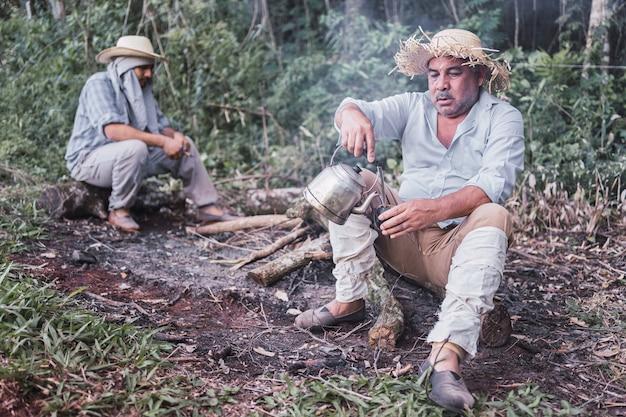 Agricultores locais tomando chá mate no intervalo em um bule rústico.
