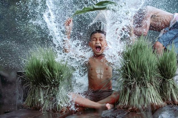 Agricultores na tailândia rural, brincando felizes na água com seu pai