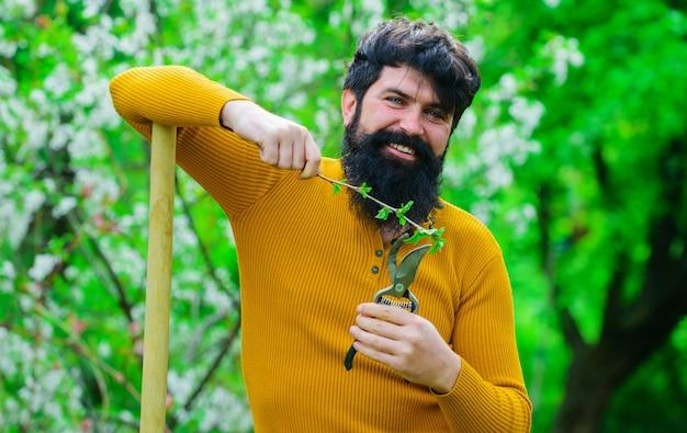 Agricultura de primavera, homem com tesouras de jardim, trabalha com ferramentas de jardinagem.