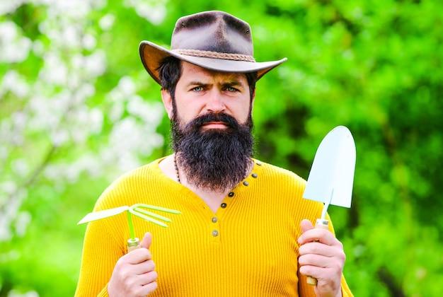 Agricultura de primavera. trabalho de jardineiro. homem barbudo com ferramentas de jardinagem. fazendeiro masculino. primavera.