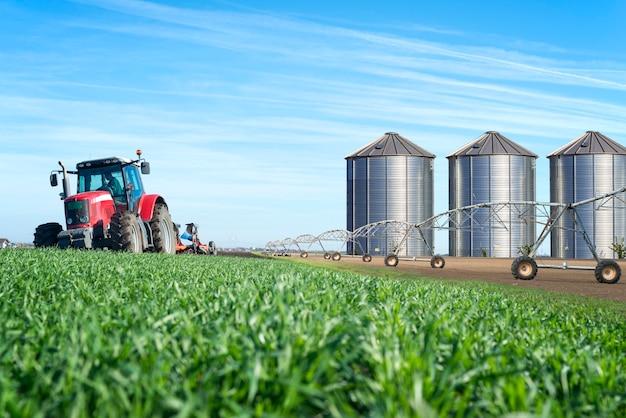 Agricultura e conceito de produção de alimentos com silos de máquina de trator e sistema de irrigação