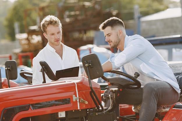 Agrônomo escolhendo uma nova plantadora. homem no terreno ao ar livre da loja. maquinaria agrícola.