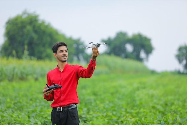 Agrônomo indiano segurando drone e controle remoto em campo agrícola