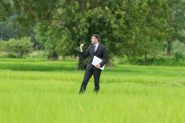 Agrônomo usando um laptop para ler um relatório e parado em um campo agrícola.