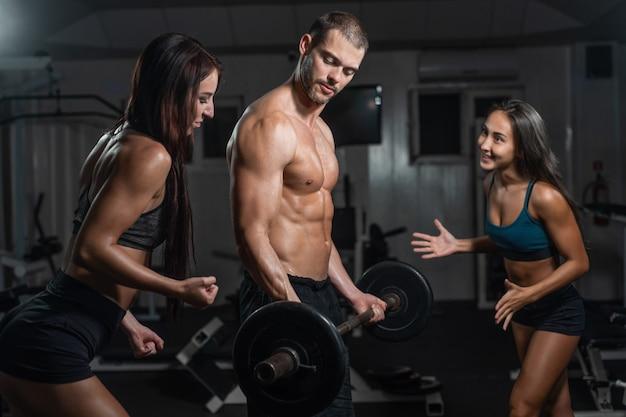 Agrupe com equipamento de treinamento do peso do dumbbell na ginástica do esporte.