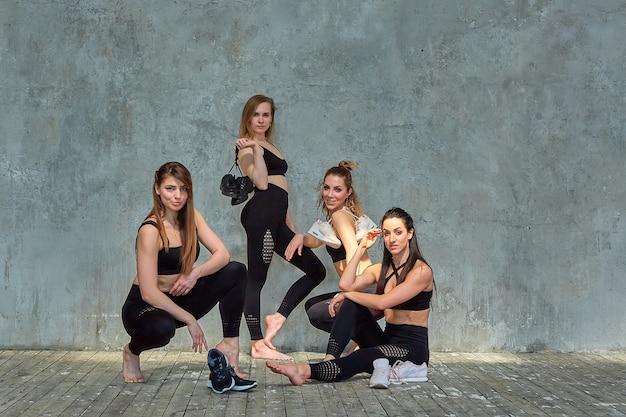 Agrupe o retrato de jovens garotas bonitas animadas desportivas com colchonetes ao lado da parede branca, rindo e conversando. alunos engraçados sinceros esperando a aula começar.