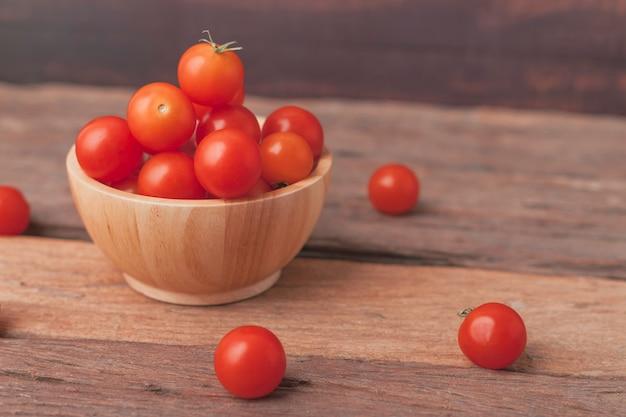Agrupe o tomate em uma tigela de madeira coloque na mesa de madeira
