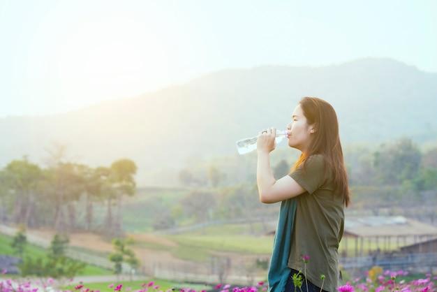 Água asiática da bebida da mulher pela garrafa ao estar no campo do cosmos, conceito da saúde.