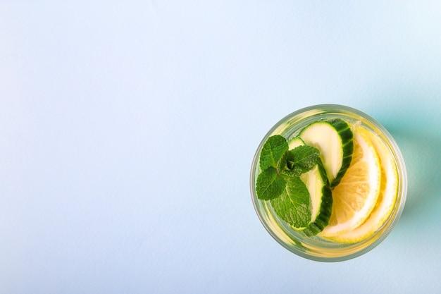 Água atrevida para desintoxicação com infusão de limão, pepino e hortelã em vidro sobre fundo azul claro. vista do topo. conceito de estilo de vida saudável. espaço para texto.