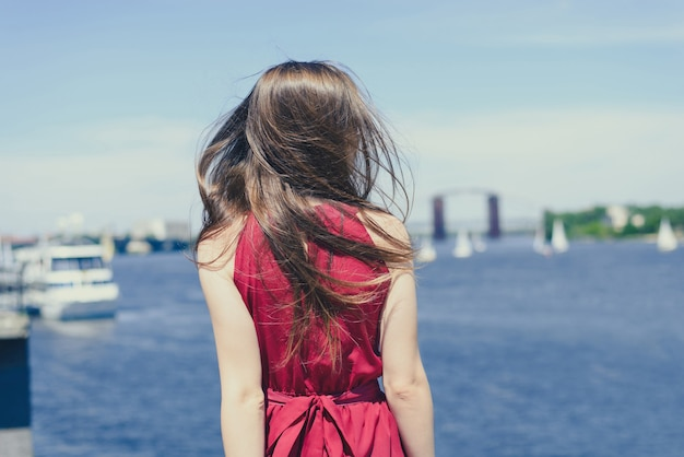 Água azul beleza natureza céu nuvens resort tour convés cruzeiro conceito. retrovisor das costas para trás foto do retrato de uma linda moça olhando para o lago perto da cidade usando um traje elegante cor de vinho brilhante