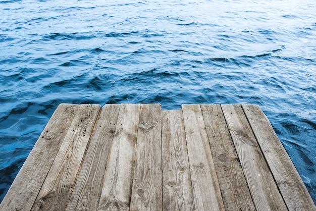 Água azul com plataforma de madeira vazia. fundo natural