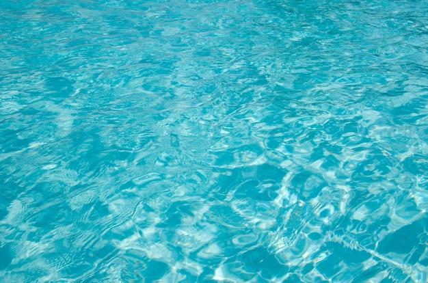 Água azul da piscina com reflexos do sol