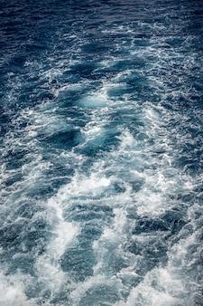 Água azul de superfície abstrata. a superfície da água azul abstrata refletia a luz solar para o fundo. mar azul
