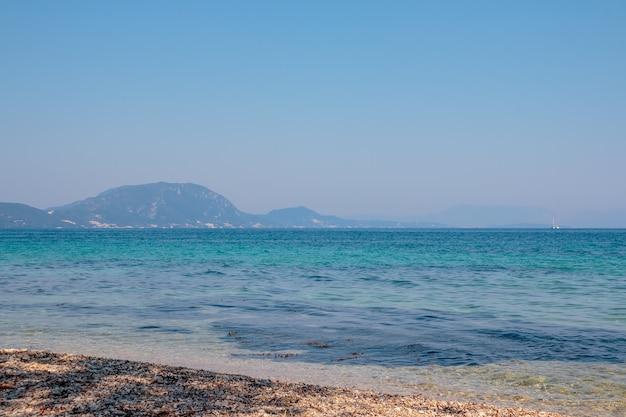 Água azul do mar e montanhas como pano de fundo. céu azul claro, sem nuvens e horizonte da montanha. conceito de cruzeiro do mar. férias de verão. copie o espaço