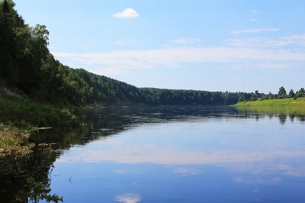 Água azul em um lago de floresta com pinheiros em um dia de verão