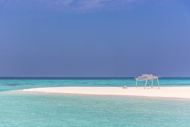 Água azul incrível em uma ilha deserta em um dia de céu azul com uma pequena cabana de madeira