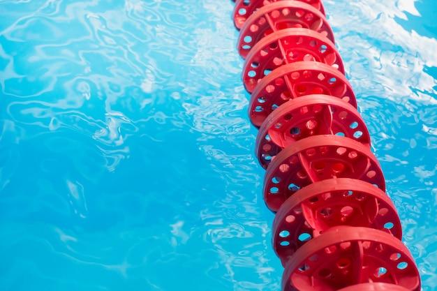 Água azul piscina e marcador de pista de natação vermelho