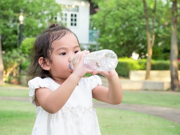 Água bebendo da menina bonito asiática pequena da garrafa plástica após o jogo que corre no parque.