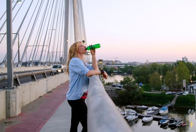 Água bebendo da mulher sedento no exercício ao ar livre na ponte da cidade.