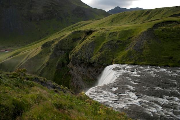 Água branca que flui sobre um penhasco cercado por prados verdes nas montanhas