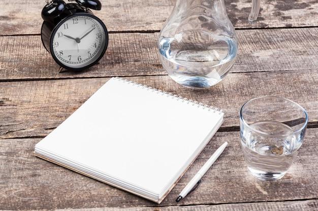 Água, caderno espiral e caneta em cima da mesa de madeira