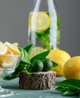 Água cítrica com folhas de limão, placa de madeira em uma garrafa na superfície de gesso e cinza de hortelã