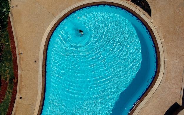 Água clara da cor azul da piscina e povos que apreciam no dia ensolarado do verão e no ângulo de vista superior.