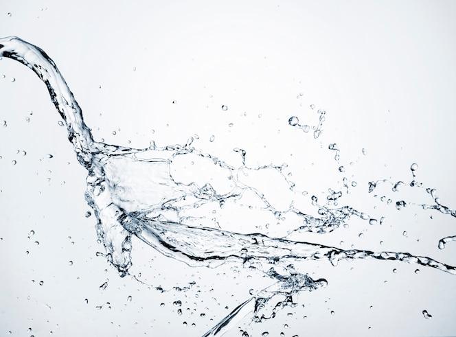 Água clara de close-up dinâmica na luz de fundo