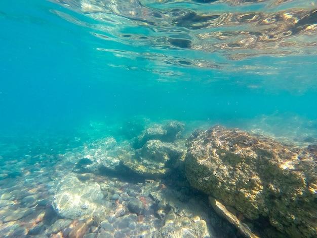 Água clara subaquática e dia rochoso do mar
