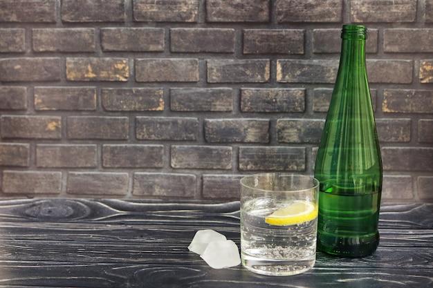 Água com gás com gelo em uma garrafa de vidro e copo