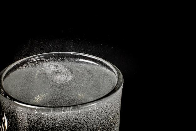 Água com gás fizz refrescante borbulhante soda pop com cubos de gelo. refrigerante frio carbonatado líquido fresco e fresco gelado em um copo. refrescante e sacie o conceito de sede.