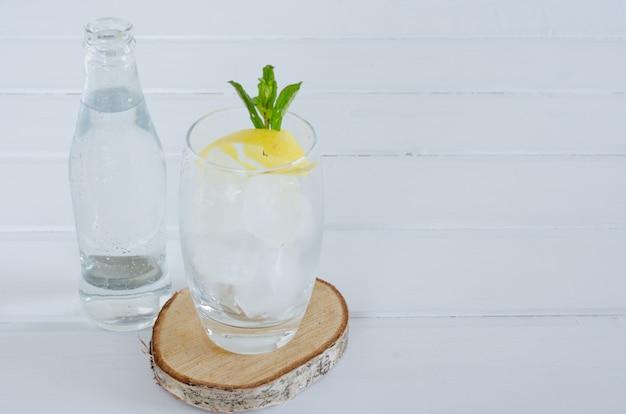 Água com gás no copo de vidro com ramo de limão e hortelã sobre fundo branco de madeira.