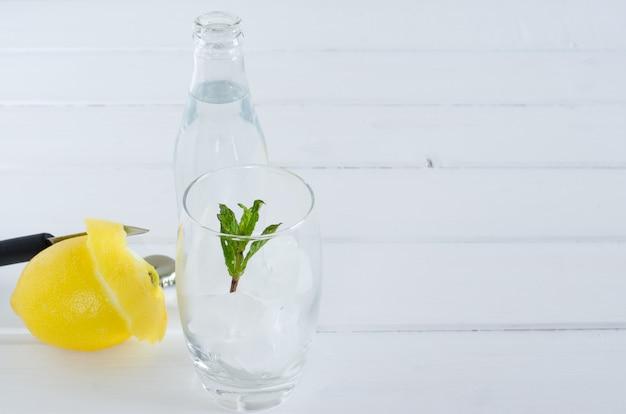 Água com gás no copo de vidro no fundo branco de madeira.