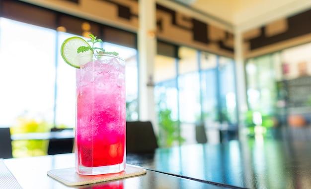 Água com gás soda red com gelo em um copo na mesa, hora do almoço.