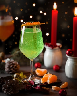 Água com gás verde na mesa de natal com velas vermelhas