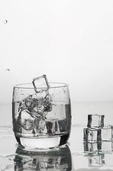 Água com gelo em um copo com salpicos