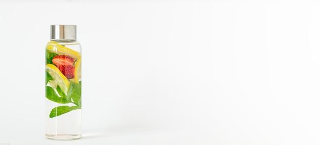 Água com infusão com sabor de limão, morango e menta. bebida refrescante de verão. cuidados de saúde, fitness, conceito de desintoxicação de dieta de nutrição saudável. fundo branco, banner, copie o espaço.