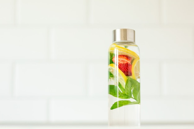 Água com infusão com sabor de limão, morango e menta. bebida refrescante de verão. cuidados de saúde, fitness, conceito de desintoxicação de dieta de nutrição saudável. fundo branco, copie o espaço.