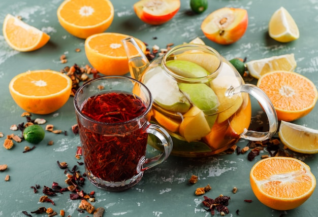 Água com infusão de frutas com chá de ervas, laranjas, limões e limas em um bule de chá na superfície de gesso