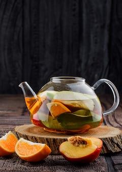 Água com infusão de frutas com frutas, madeira no bule de chá na telha de pedra e superfície de madeira