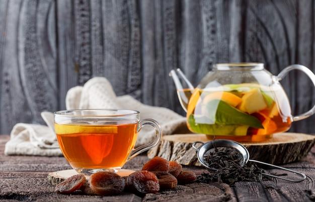 Água com infusão de frutas no bule com chá, damascos secos, madeira, toalha de cozinha, vista lateral do recipiente na telha de pedra e superfície de madeira