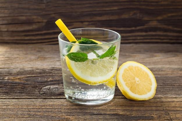 Água com limão e hortelã em um copo de madeira