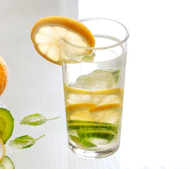 Água com limão e pepino em um copo. bebida desintoxicante.
