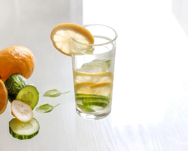 Água com limão e pepino em um copo sobre um fundo claro. bebida desintoxicante.
